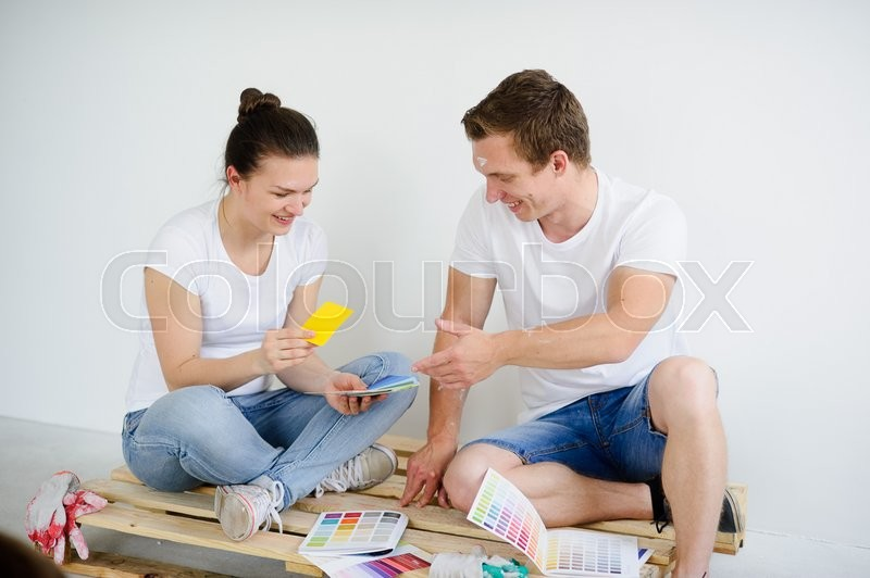 Stock image of 'Young people select color for coloring of walls in the room. The guy and the girl sit on a floor in the empty room. They examine samples. On faces of a smile. Near them working gloves and catalogs.'