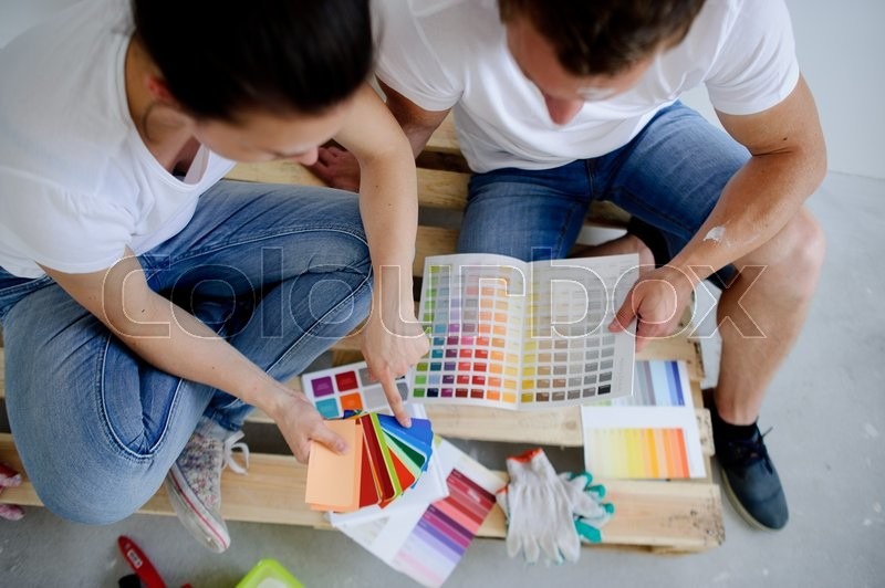 Stock image of 'The girl and the guy to pick a color for painting walls Young people sit hunched over catalog. They pick the color of paint. The girl points to a sample which is pleasant to her.'