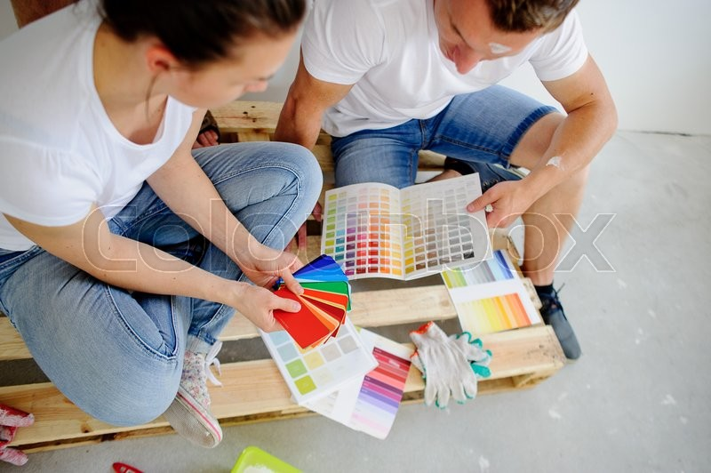 Stock image of 'Man and woman choose color of decor, sitting on a floor. They sit having inclined the heads over catalogs and pick the color of paint. The woman points to a sample which is pleasant to her.'