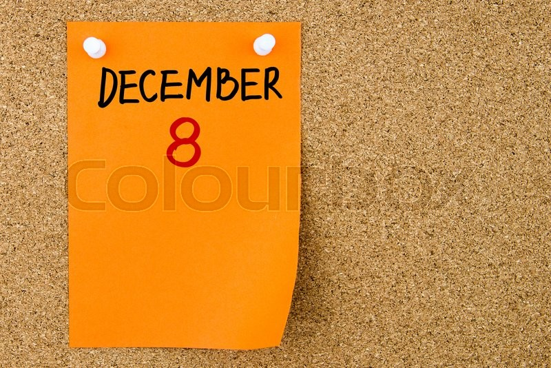 Stock image of '8 DECEMBER written on orange paper note pinned on cork board with white thumbtacks, copy space available'