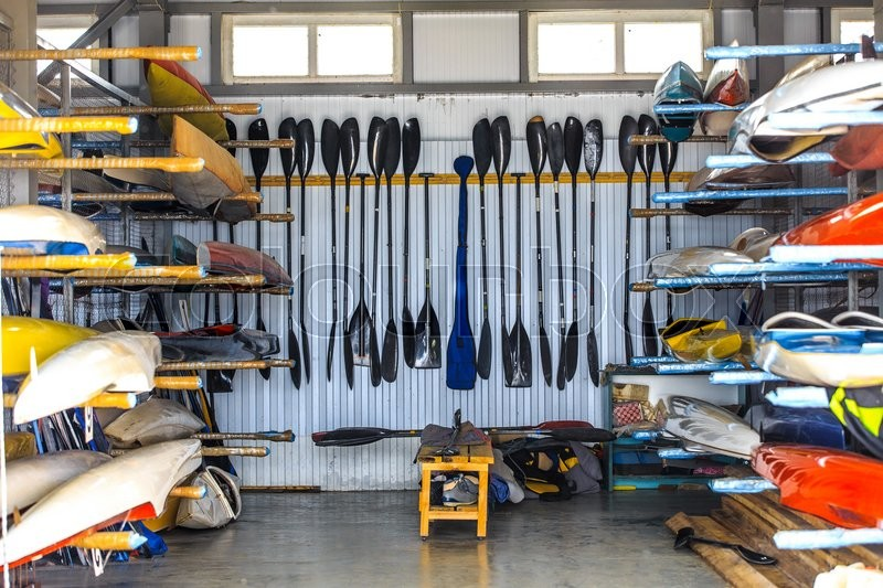 Stock image of 'warehouse for storage of boats, canoes and kayaks, paddle'