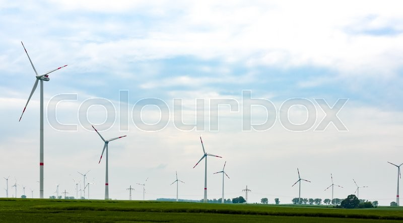 Stock image of 'Panorama of the field with eco electric windmills.Windmills outdoor under blue sky on green field.Group of eco windmills for renewable electric energy production.'