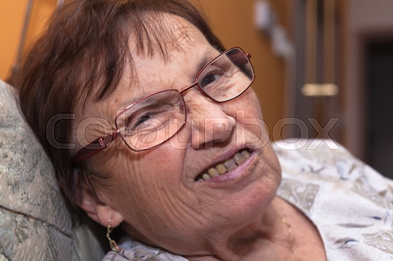 Stock image of 'Closeup of a senior woman grimacing and frowning.'