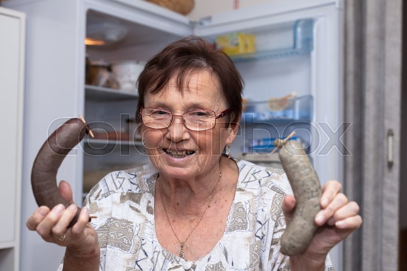 Stock image of 'Happy senior woman holding pork liver sausages while standing in front of the open fridge in the kitchen.'