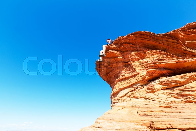 Stock image of 'Man on the sheer cliff'