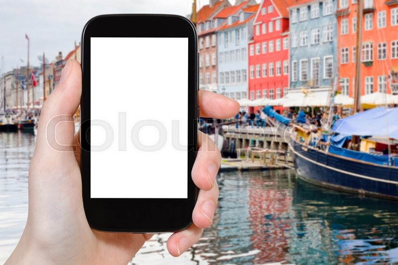 Editorial image of 'travel concept - tourist photographs Nyhavn (New Harbour) in Copenhagen, Denmark on smartphone with cut out screen with blank place for advertising'