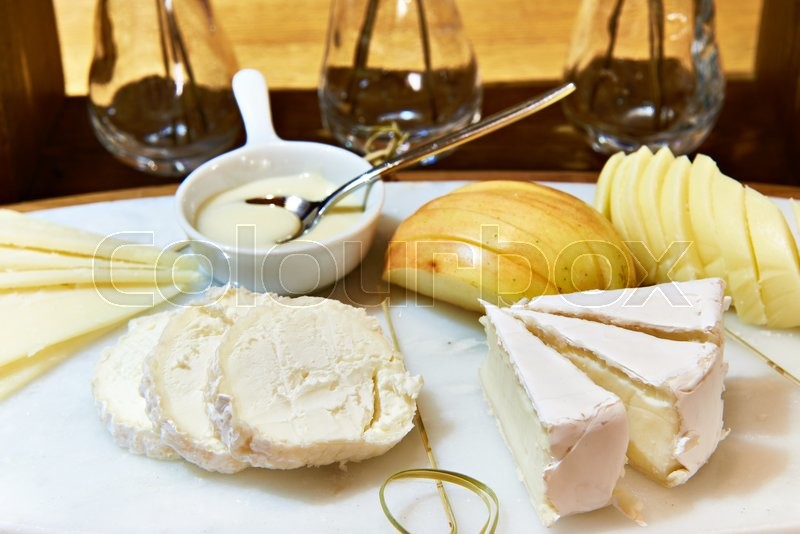 Stock image of 'Cheese plate with camembert, buche, apple and honey on the dining table'