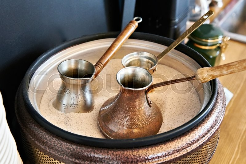 Stock image of 'Preparation of Turkish coffee in the cezve in the sand at the cafe bar'