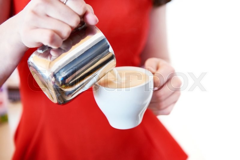 Stock image of 'Girl in red is preparing a cappuccino in a cafe bar'