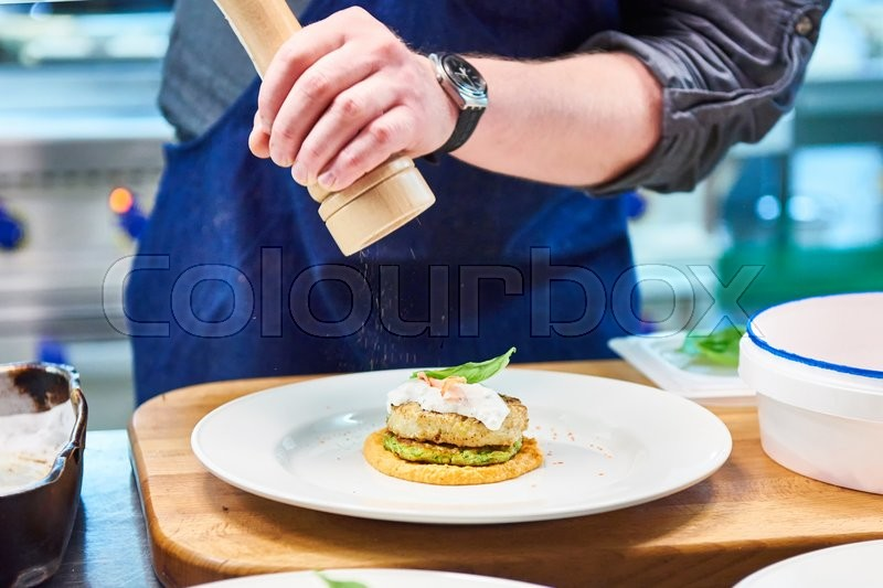 Stock image of 'Cook sprinkles seasoning in the dish with fish cutlet in a restaurant'