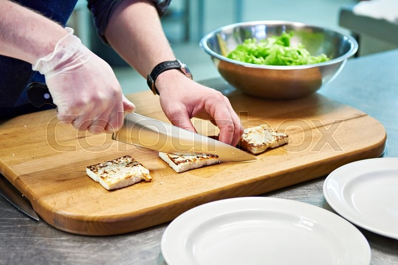 Stock image of 'Preparing dishes of fried cheese and green salad in restaurant'