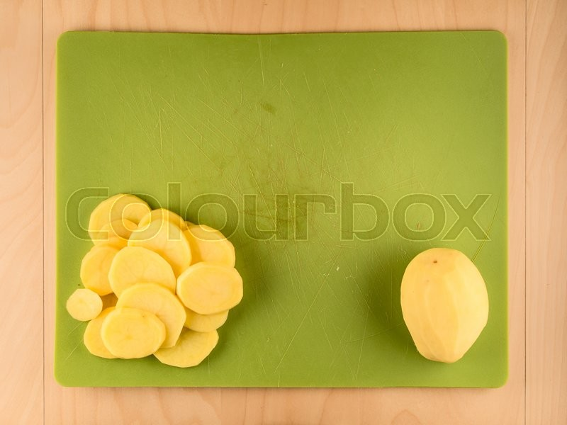 Stock image of 'Whole and sliced potatoe on green plastic board'
