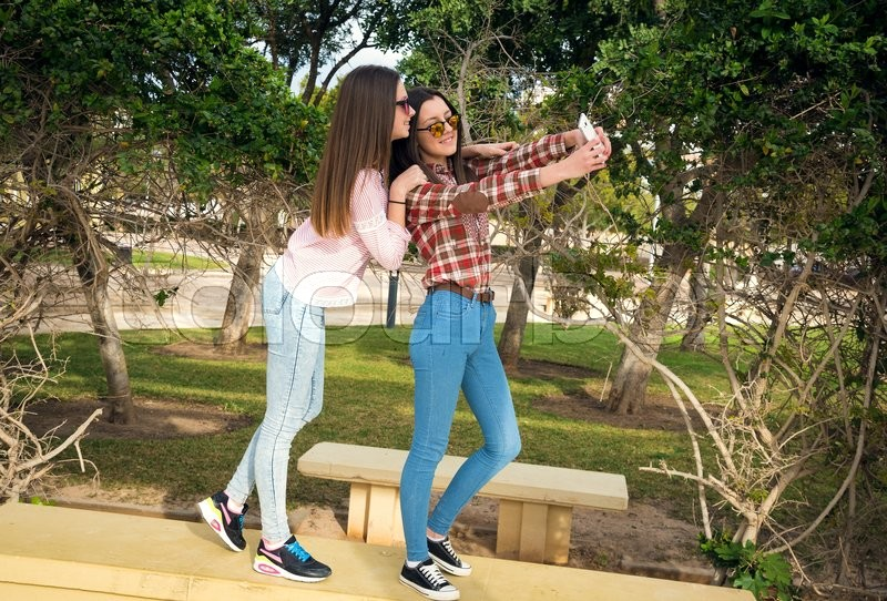 Stock image of 'two girls doing selfie in park'