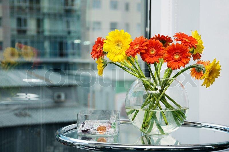 Blumenstrauß aus Rosen in einem Glas runde Vase auf einem Glastisch ...