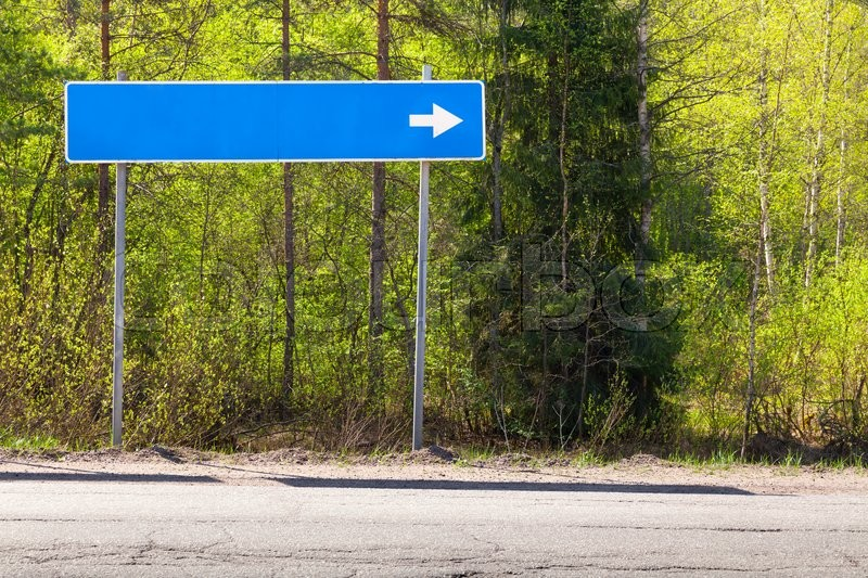 Blue road sign near highway with blank place for destination name and white direction arrow, stock photo