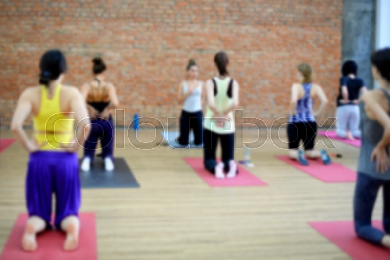 Stock image of 'Blurred image of young women doing yoga indoors. Group workout in yoga studio. Selective focus'