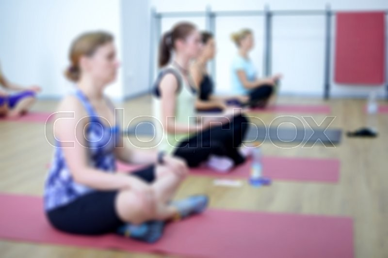 Stock image of 'Blurred image of young women doing yoga indoors. Group workout in yoga studio'