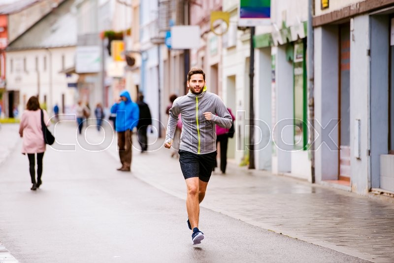 Stock image of 'Young hipster man in gray sweatshirt running in town, main street'