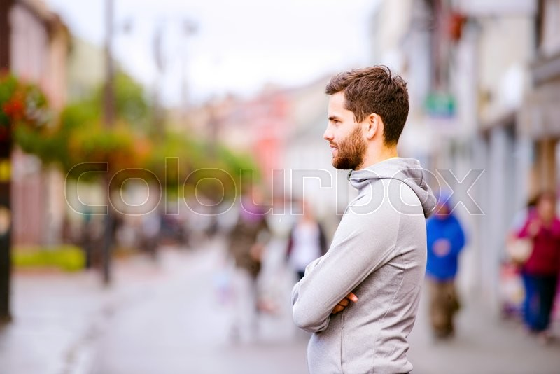 Stock image of 'Young hipster man in gray sweatshirt running in town, resting, main street'