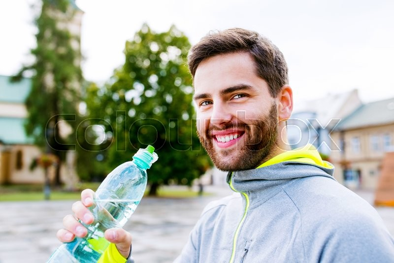 Stock image of 'Close up of young hipster runner in town with water bottle, drinking'