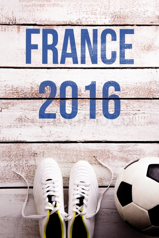 Stock image of 'Soccer ball, cleats and France 2016 against wooden floor, studio shot on white background.'