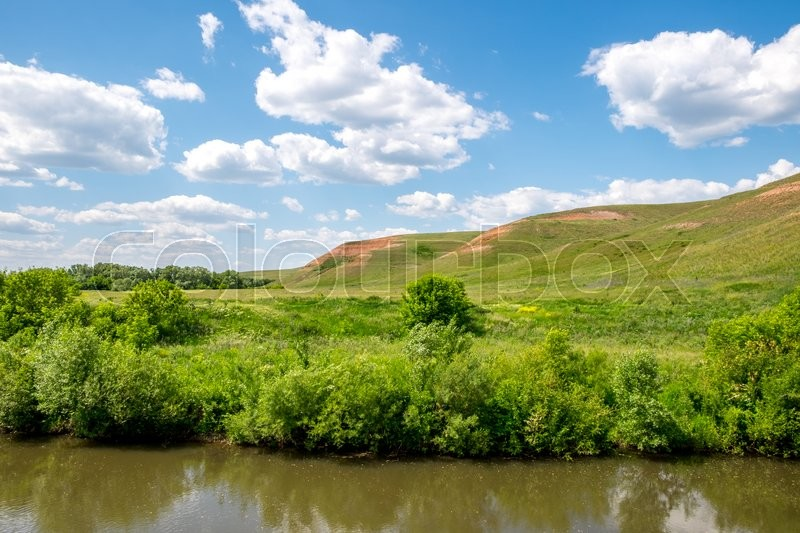 Stock image of 'Quiet river with hills, blue sky and clouds'