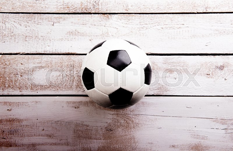 Stock image of 'Soccer ball against wooden floor, studio shot on white background. Copy space.'