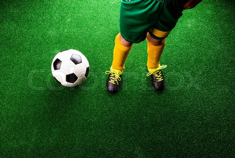 Stock image of 'Legs of unrecognizable little football player with soccer ball against artificial grass. Studio shot on green grass.'