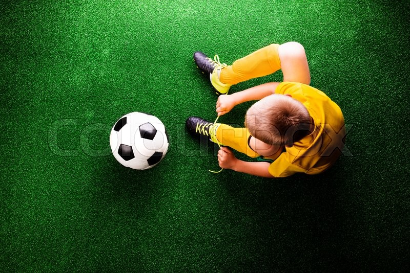 Stock image of 'Unrecognizable little football player with soccer ball tying shoelaces, against artificial grass. Studio shot on green grass.'
