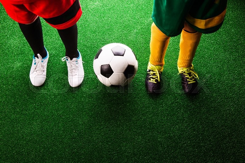 Stock image of 'Legs of two unrecognizable little football players with soccer ball against artificial grass. Studio shot on green background.'