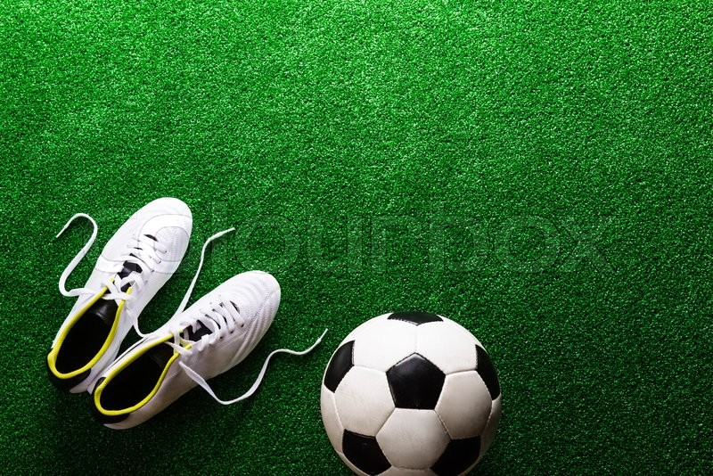 Stock image of 'Soccer ball and cleats against artificial turf, studio shot on green background. Copy space.'