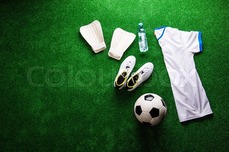 Stock image of 'Soccer ball,cleats and various football stuff against artificial turf. Studio shot on green background. Copy space.'