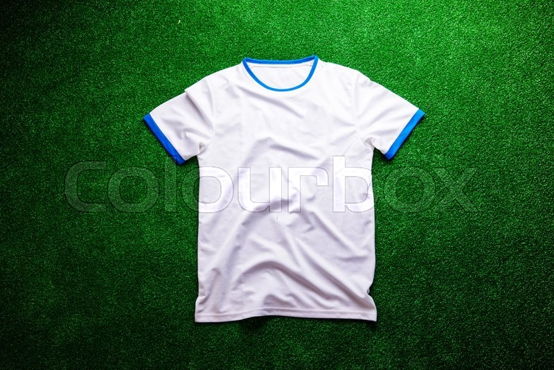 Stock image of 'White sports t-shirt against artificial turf, studio shot on green background. Copy space.'