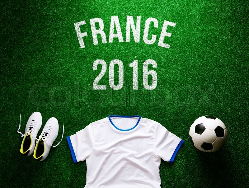 Stock image of 'Soccer ball, cleats, white t-shirt and France 2016 sign against artificial turf. Studio shot on green background.'