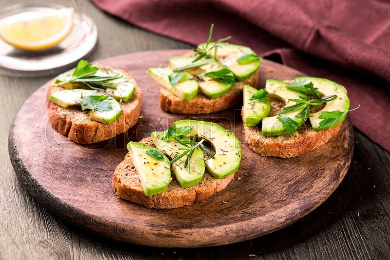 Stock image of 'Toast with rye bread and avocado, herbs on wooden board'