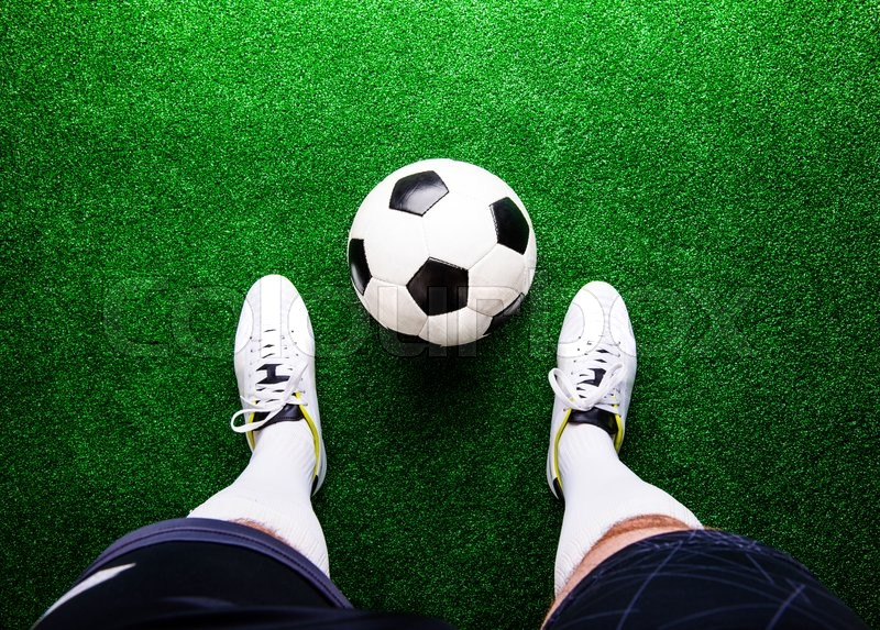 Stock image of 'Legs of unrecognizable football player against artificial grass. Studio shot on green grass.'