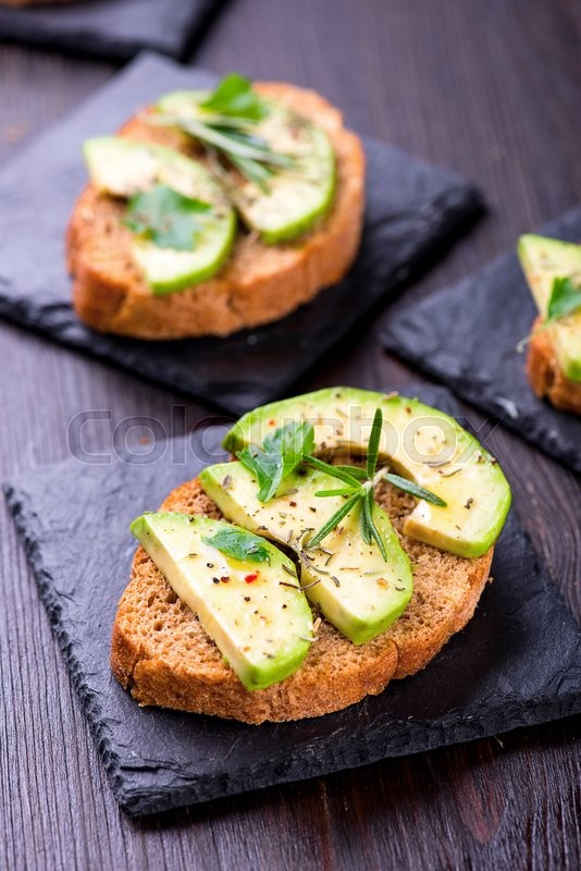 Stock image of 'Toast with rye bread and avocado, herbs on slate board'
