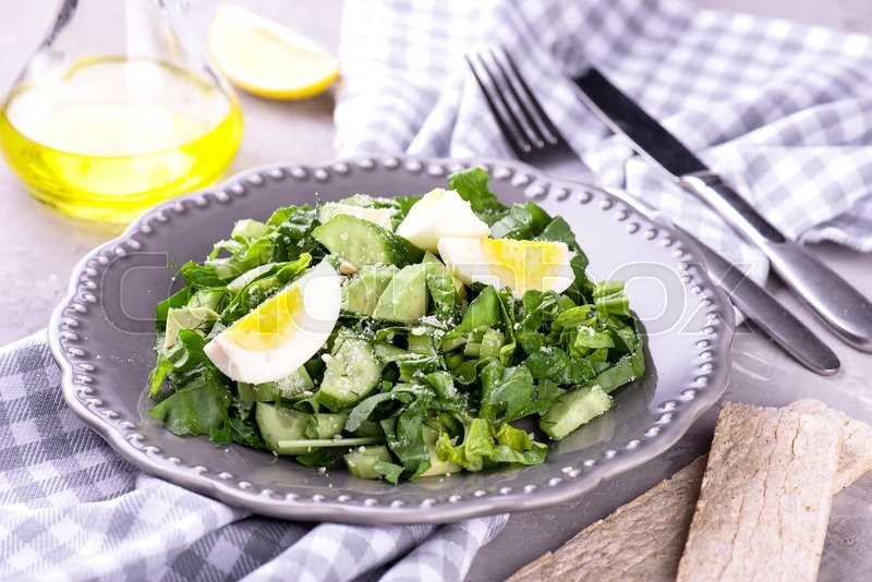 Stock image of 'Fresh spinach and avocado salad on grey plate'