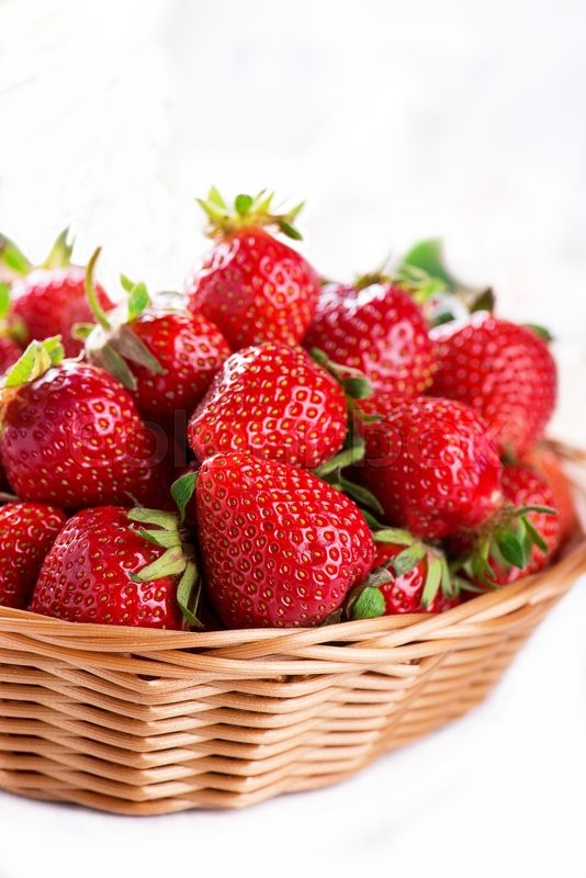 Stock image of 'Fresh strawberry harvest in the basket, isolated on white'