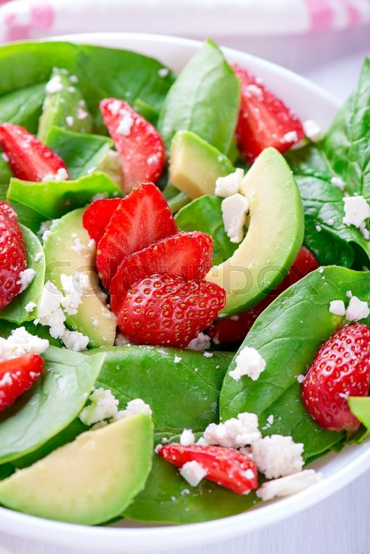Stock image of 'Summer salad with strawberry, avocado and spinach. White table. '