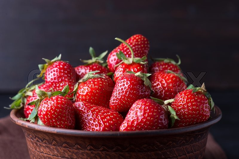 Stock image of 'Fresh strawberry in the brown bowl, dark background'