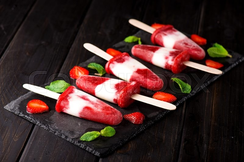 Stock image of 'Homemade strawberry yogurt ice cream popsicles on slate'