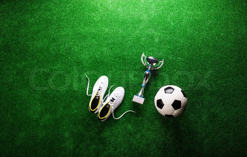 Stock image of 'Soccer ball, cleats and trophy against artificial turf, studio shot on green background. Copy space.'