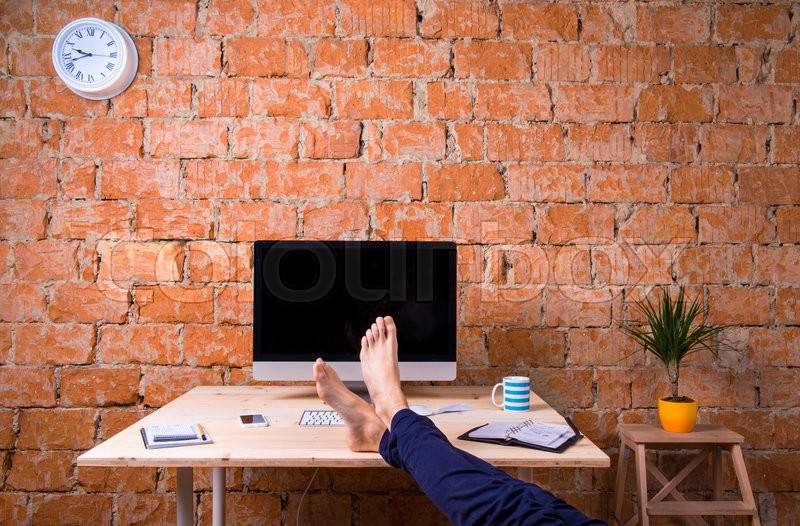 Stock image of 'Feet of unrecognizable businessman sitting at his office desk. Brick wall background. Smart phone, tablet and various office supplies around the workplace. Flat lay.'
