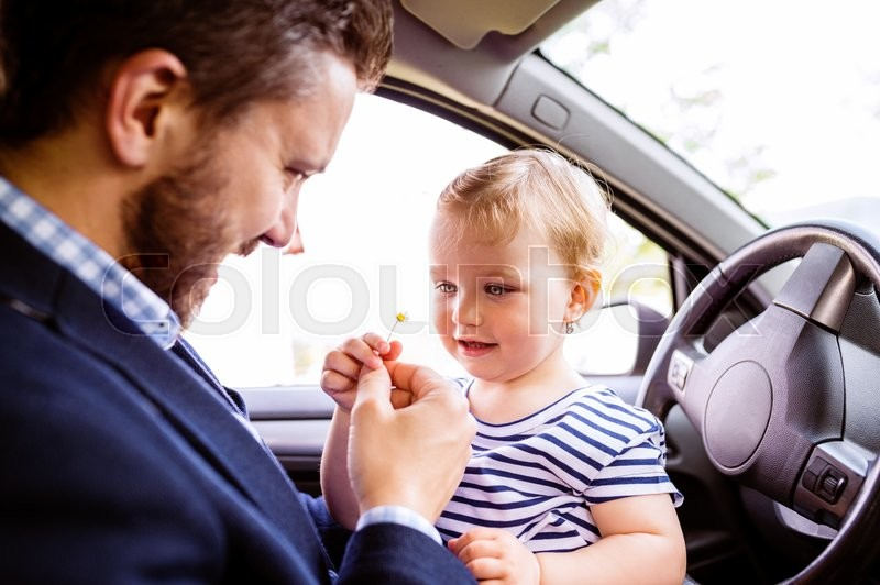 Stock image of 'Close up of hipster father with his little daughter sitting in the car, giving her little daisy flower'