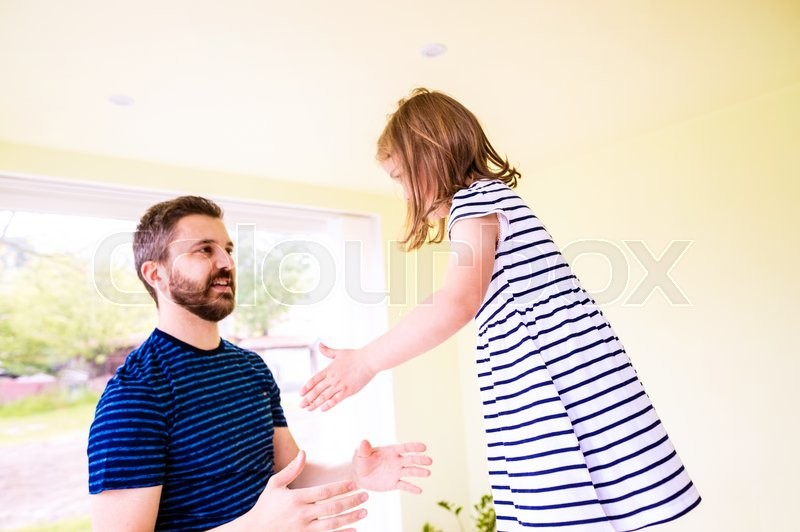 Stock image of 'Hipster father with his cute little daughter jumping into his arms, wearing blue striped dress'