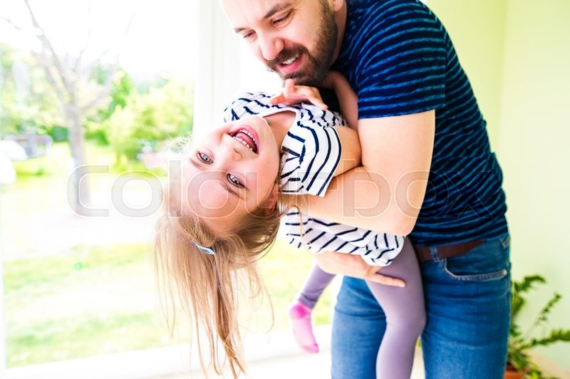 Stock image of 'Close up of hipster father holding his little daughter, sunny day'