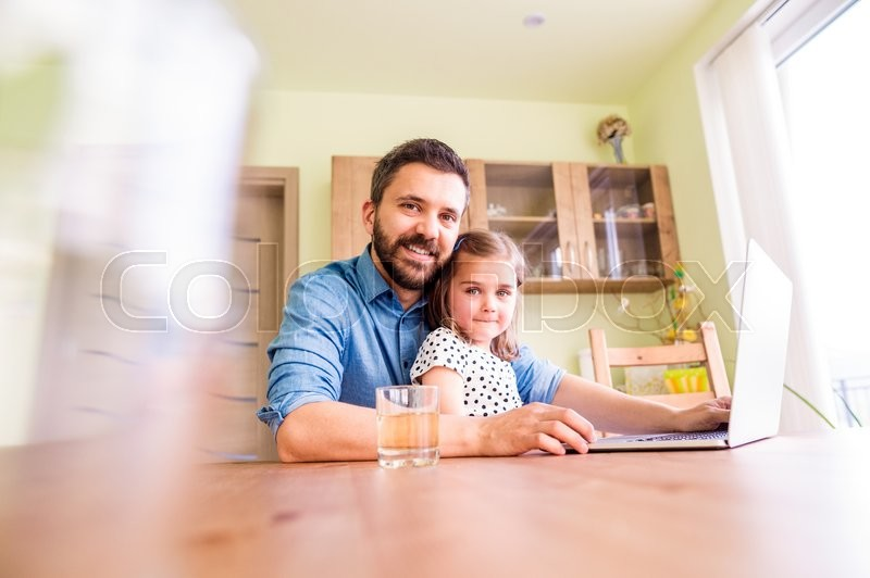 Stock image of 'Father and daughter together, playing on laptop, sitting at the kitchen table'