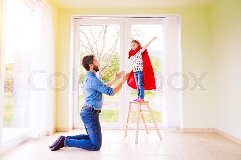 Stock image of 'Hipster father with his cute little princess daughter jumping into his arms, wearing red cape'