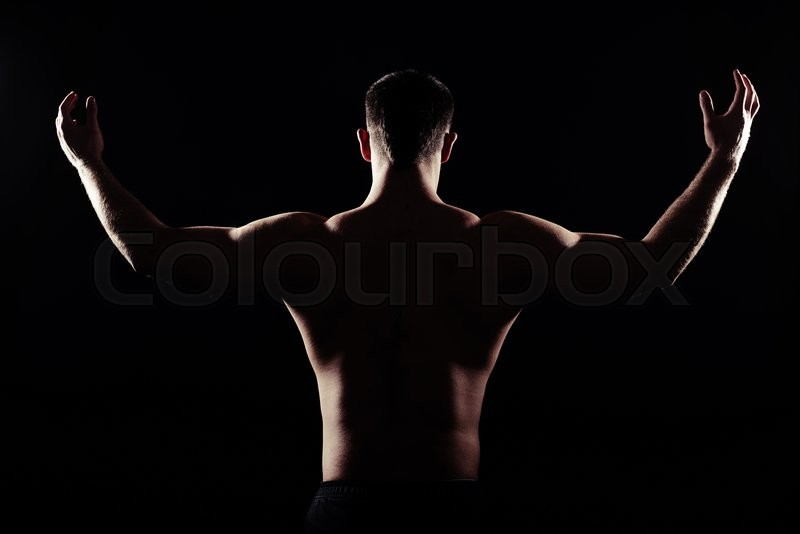 Stock image of 'Back view of sexy athletic guy with bare torso who is showing muscles with his hands raised isolated on black background'